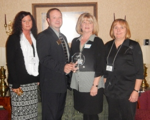 David Hill, Chamber President, presents Tina Hughes, Denise Christescu, and Christine Ferraro with Westbrook Village Apts./K&D with their award.